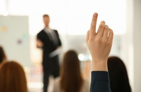 Young,Woman,Raising,Hand,To,Ask,Question,At,Business,Training